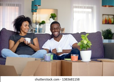 Happy African American young couple relax on couch drinking tea making break on moving day, smiling black family take pause in unpacking enjoying coffee on sofa laughing and having fun together