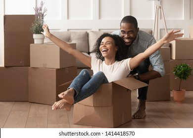 Happy african american young couple first time home buyers having fun unpacking laughing on moving day, excited wife riding sitting in cardboard box while black husband push it in new house apartment