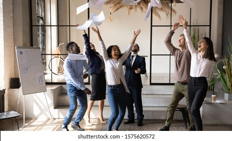 Happy african american young employee tossing papers up, enjoying friday party with overjoyed different generations mixed race coworkers, celebrating corporate success win achievement at office.