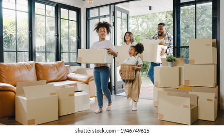 Happy African American young family bought new house. Mom, Dad, and child smiling happy hold cardboard boxes for move object walking into big modern home. New real estate dwelling, loan and mortgage.