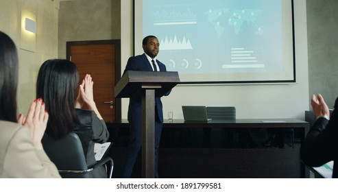 Happy African American young and handsome man in business style finishing his speech at the conference or report in front of colleagues and leaving the auditory while people applauding.