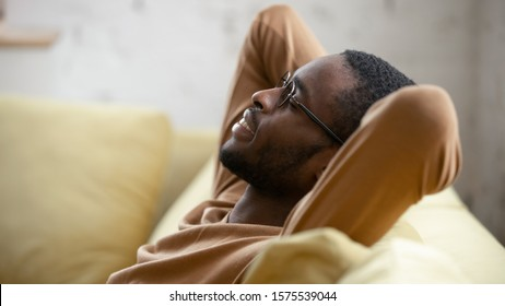 Happy african American young man in glasses sit relax on cozy couch lean hands over head taking nap in living room, smiling biracial male rest on sofa at home sleeping or dreaming, stress free concept