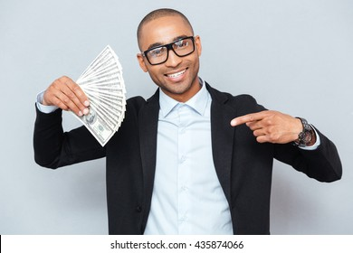 Happy african american young man holding dollars and pointing on it