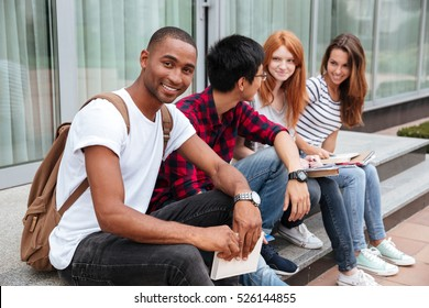 Happy african american young man student sitting with his friends outdoors