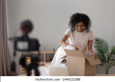Happy african american young woman vlogger open parcel shooting video blog on camera make review on internet shopping order at home, smiling black girl blogger recording vlog for online channel