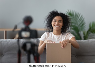 Happy african american young woman blogger open parcel shooting video blog on camera, smiling black girl vlogger make review on internet shopping order at home recording vlog for online channel