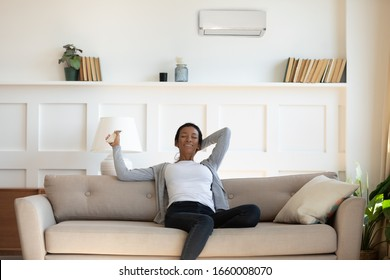 Happy African American young woman relax on sofa in living room turn air condition device, calm biracial female rest on comfortable couch at home use remote controller, switch AC conditioner