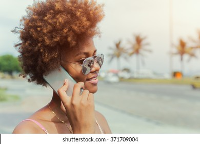 Happy african american young woman in sunglasses calling on smartphone, ocean beach in the background