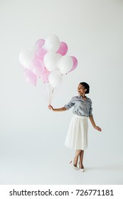 happy african american young woman holding bunch of balloons isolated on grey