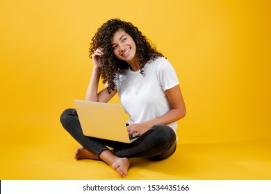 happy african black woman sitting with laptop isolated over yellow