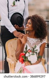 Happy african bride and groom with bouquet of red flowers softly holding hands
