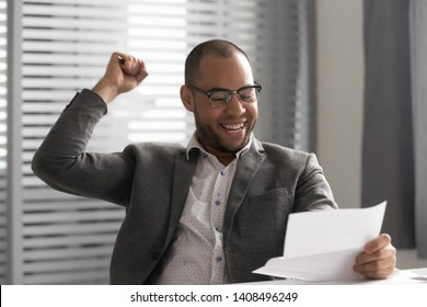 Happy african business man winner holding reading postal mail letter excited by good news got new job celebrating taxes refund overjoyed by bill loan approval receiving salary rise payment in office