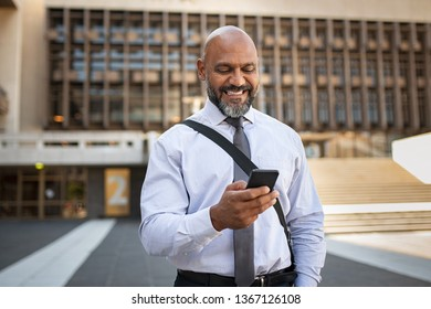 Happy african businessman holding mobile phone while walking on city street. Smiling mature business man using app on smartphone outdoor. Senior professional black man using cellphone in city centre.