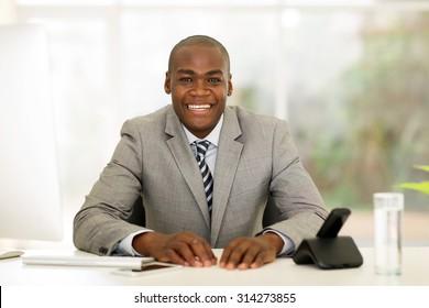 happy african businessman sitting in modern office