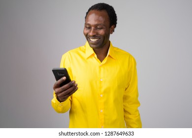 Happy African businessman smiling while using phone