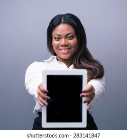 Happy african businesswoman showing tablet computer screen over gray background. Looking at camera