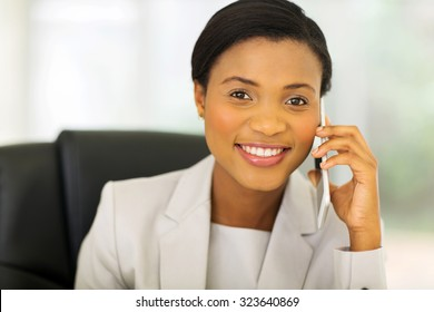 happy african businesswoman talking on mobile phone in office