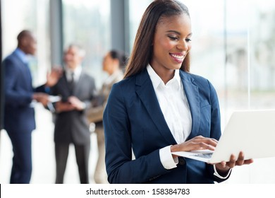 happy african businesswoman working on laptop computer