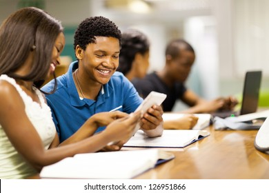 happy african college students using tablet computer together