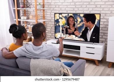 Happy African Couple Sitting On Sofa Watching Television At Home