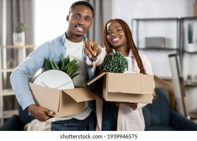 Happy african couple smiling and hugging at new apartment with boxes around. Young family showing on camera keys from flat. Concept of house ownership.