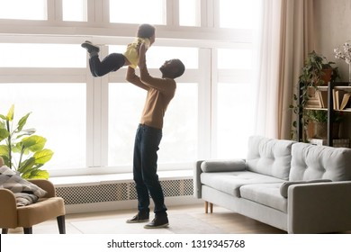 Happy african dad lifting little toddler son up playing at home, loving black dad holding kid boy having fun in modern living room together, small child enjoying weekend activity time with father