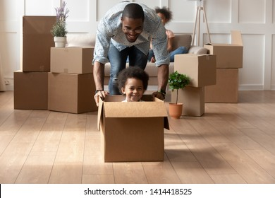 Happy african dad playing with cute little mixed race son looking at camera laughing on moving day, black father having fun with kid boy riding in box in living room, relocation, new house purchase