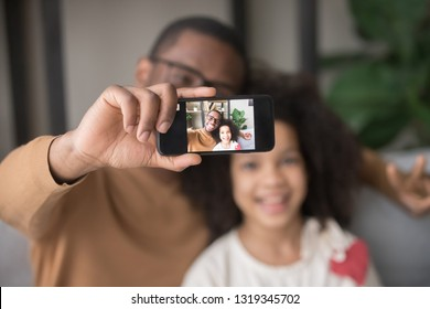 Happy african dad taking selfie with kid daughter on cellphone, smiling black father holding phone making pic on modern smartphone camera, daddy and child focus portrait picture on mobile display