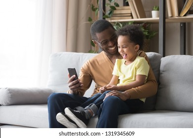 Happy african dad and toddler child son laughing looking at cellphone using funny smartphone mobile face app sitting on sofa, black father holding phone taking selfie with cute little kid boy at home