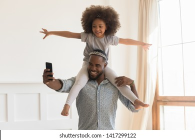 Happy african dad wearing crown piggybacking little funny daughter taking selfie at home, loving black father carrying cute small kid on back holding phone make photo playing together in living room