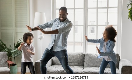 Happy African ethnicity father have fun teaches little preschool kids to dance in modern living room at home. Dad with son and daughter engaged in funny activity enjoy leisure carefree weekend concept - Shutterstock ID 1687124713