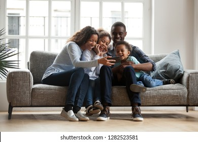 Happy african family with 2 children son daughter having fun with gadget on couch using smartphone at home, black parents and kids laugh watch funny video, make video call selfie on phone online app