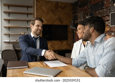Happy African family after sign contract shake hands bank advisor. Make financial deal at meeting, successful negotiations, real estate buyers making deal with male broker agent, take mortgage concept