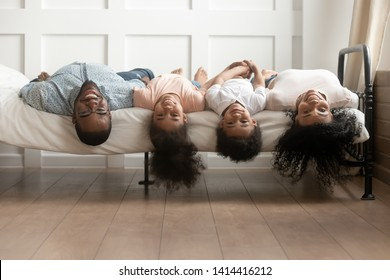 Happy african family bonding lying upside down on bed, young black parents and cute little kids posing for funny portrait in bedroom, mixed race mom dad with small children look at camera having fun