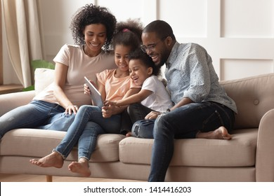 Happy african family having fun with device at home, black parents and little children using digital tablet looking at screen sit on sofa together, cute kids hold computer laugh watch cartoons online