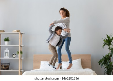 Happy african family mixed race ethnicity kid boy and mom baby sitter hold hands jumping on bed mattress, cheerful mother having fun laughing playing funny active game with cute child son in bedroom