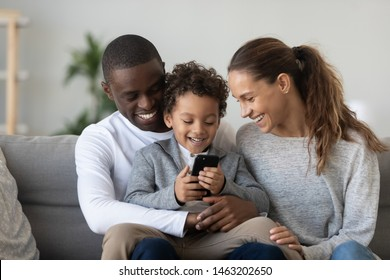Happy african family mixed race ethnicity parents with small cute little kid child son sit on sofa laughing having fun holding smart phone using funny mobile app watching videos on cellphone at home