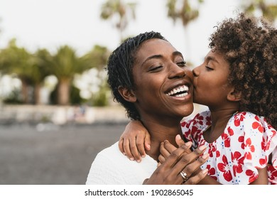 Happy African family on the beach during summer holidays - Afro American people having fun on vacation time - Parents love unity and travel lifestyle concept