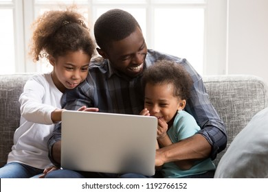 Happy African family spend time have a fun together using computer at home. Black father with little preschool daughter and toddler son watching funny video laughing sitting on couch at sitting room