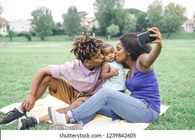 Happy african family taking a selfie with mobile smart phone camera in a public park outdoor - Mother and father having fun with their daughter during a weekend sunny day - Love and happiness concept