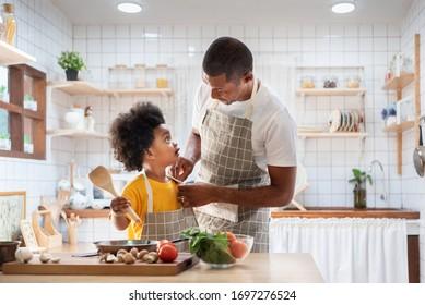 Fröhlicher afrikanischer Vater und Sohn kleiden sich zusammen, bevor sie in der weißen Küche kochen. Ein Papa-Chef mit schwarzem Kinderhelfer in gelbem Hemd, der zu Hause Essen zubereitet. Augenkontakt, Beziehung, warme Familie