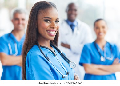 happy african female nurse with colleagues on background