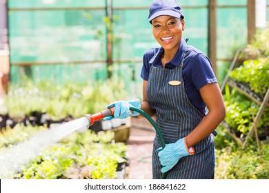 happy african female nursery worker watering plant