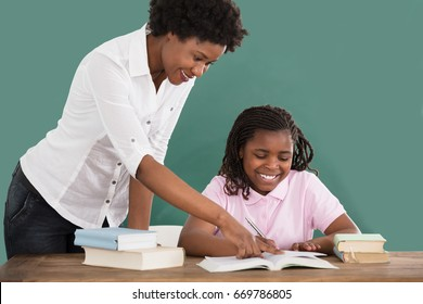 Happy African Female Teacher Helping Her Student In Homework At Classroom