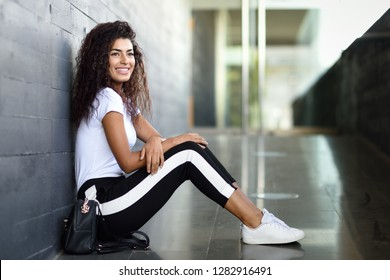 Happy African girl with black curly hairstyle sitting on urban floor. Smiling Arab woman in sport clothes in the street.