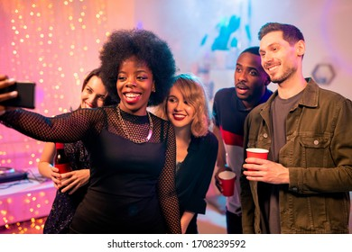 Happy African girl with toothy smile making selfie with intercultural friends while enjoying home party and having drinks together