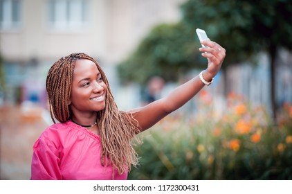 Happy African girl using mobile phone and making selfie at city street