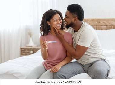 Happy african guy husband cuddling smiling wife, got positive pregnancy test, bedroom interior, copy space