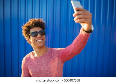 happy african guy smiling and taking a selfie photo using smartphone out on a colorful blue background