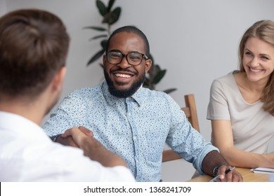 Happy african hr recruit manager handshake hire candidate at business interview, smiling black recruiter employer shake hand employ congratulate new worker made good first impression got job concept